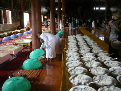 Female monks (shaved heads) preparing rice for the male monks